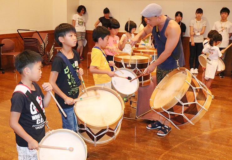 廣瀬さん(手前右)から太鼓のたたき方を学ぶ児童=南砺市福野文化創造センター