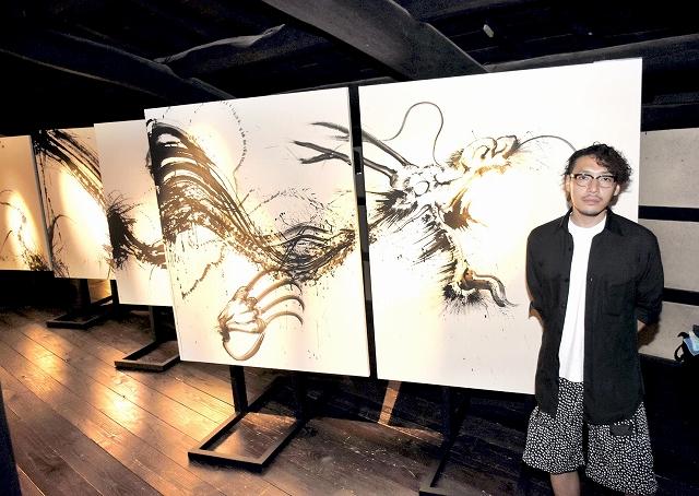黒龍を描いた作品の前に立つ西元祐貴さん=福井県越前市の卯立の工芸館