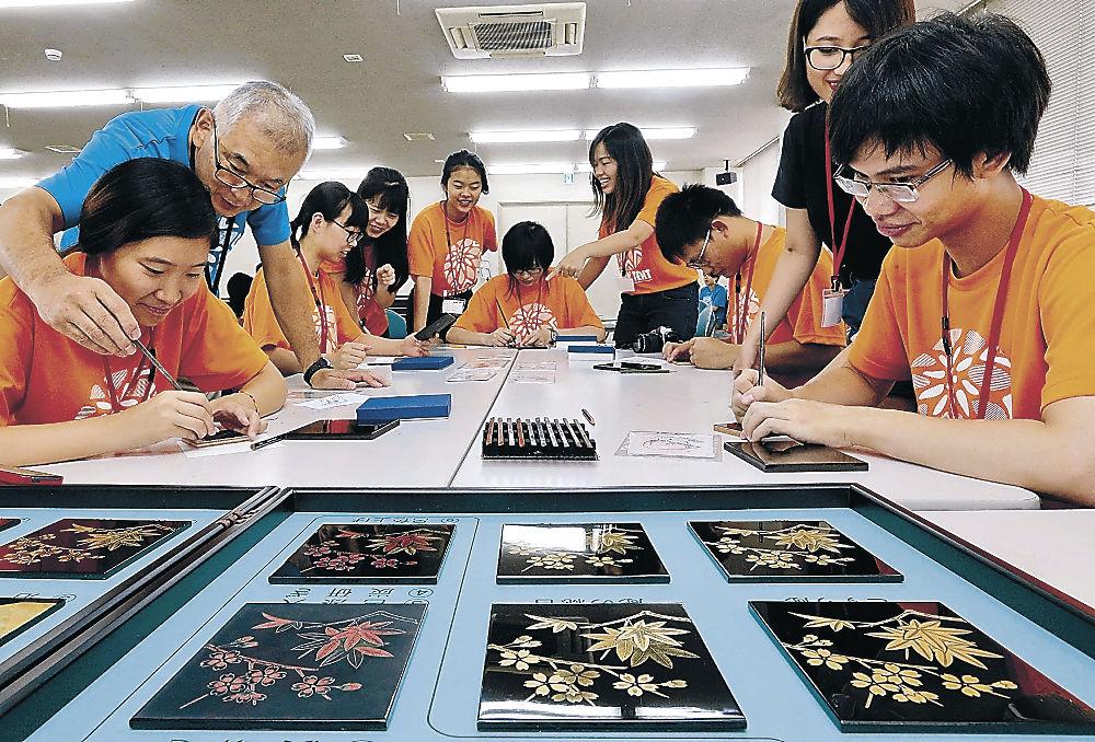 沈金の技法で輪島塗のパネルを作る留学生=輪島市役所