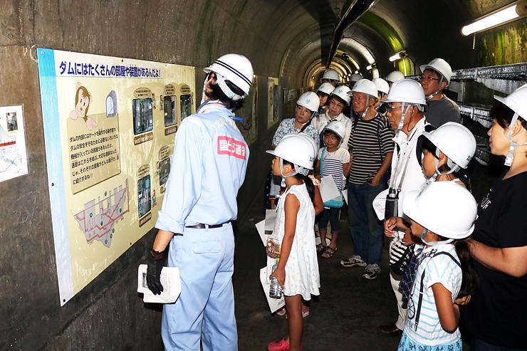 ダム内部の施設点検などに使う監査廊を見学する参加者=黒部市の宇奈月ダム