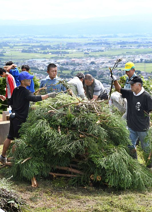 スギの枝やヨモギを積み重ねのろし台を作る参加者=20日、上越市の春日山城跡