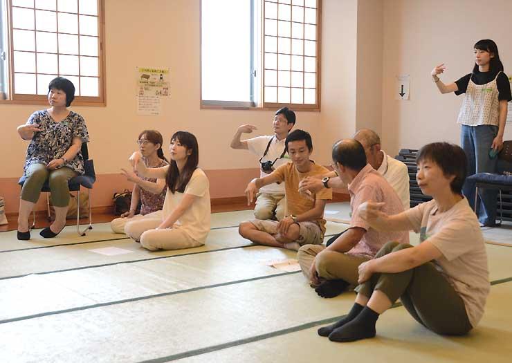 交流会で長野大生から簡単な手話を教わる参加者ら