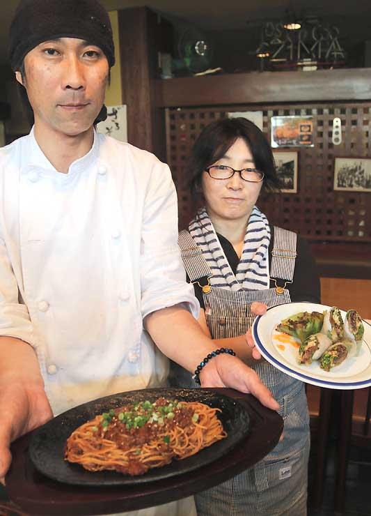 「HARADA」で提供する「こもろん味噌」のパスタや生春巻きを手にする原田良太郎さん(左)、由美子さん夫婦