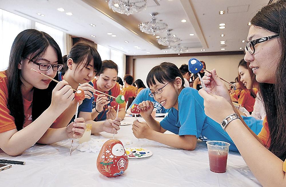 思い思いに人形を色づける留学生=金沢市のしいのき迎賓館