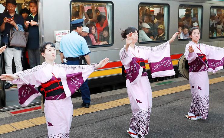 駅のホームで踊る「見送りおわら」を楽しむ観光客らで混雑する列車=2016年9月4日、JR越中八尾駅