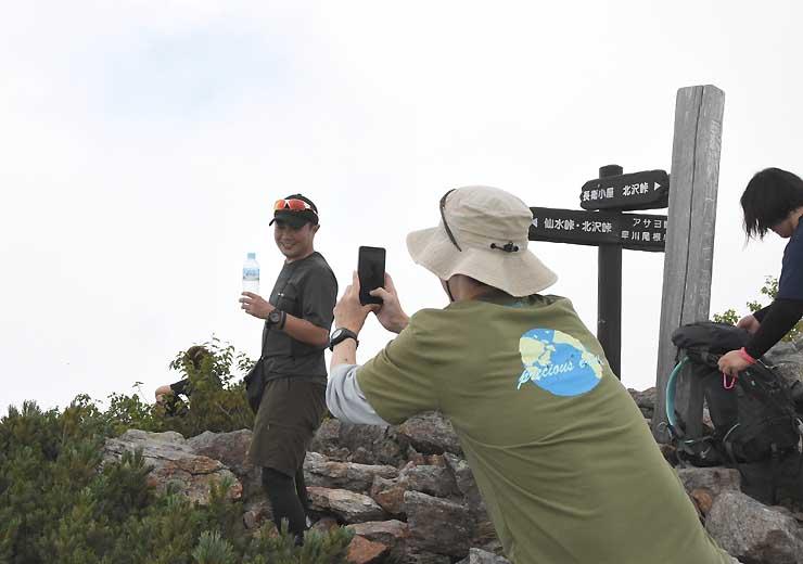 栗沢山山頂でCMの飲料水を手に写真を撮り合う登山者。気分はもう宇多田ヒカル?