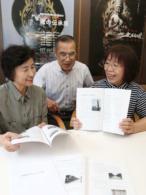 ガイド冊子を手にする新保代表(右)と会員