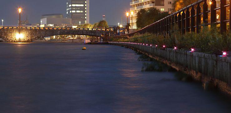 萬代橋近くの信濃川沿いに設置され、柔らかな光を放つ照明「彩り蛍」=24日夜、新潟市中央区