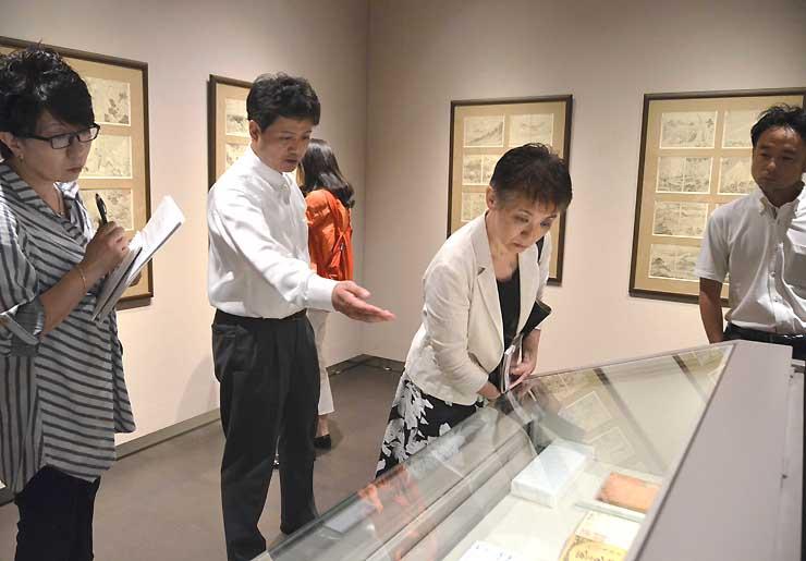 北斎館で展示されている「富嶽百景」を鑑賞するコンシェルジュの阿部さん(右から2人目)ら