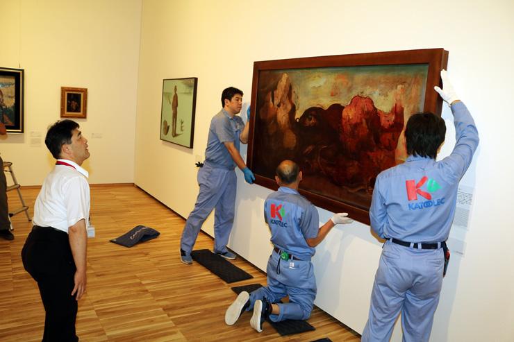 八木課長(左)が見守る中、壁に掛けられる「眼のある風景」=富山県美術館