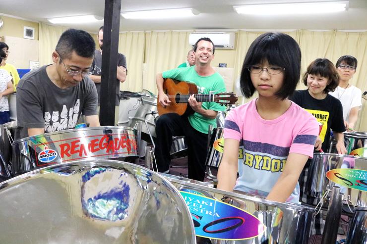 キンテーロさん(中央奥)のギターに合わせて、スチールドラムを演奏するSSOメンバー=南砺市広安の練習場