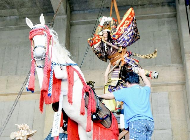クレーンで引き揚げられた武者人形を山車に設置する参加者=27日、福井県敦賀市のみなとつるが山車会館