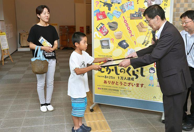 1万人目の来場者となり、記念品を受け取る男子児童(中央)=25日、長岡市の県立歴史博物館