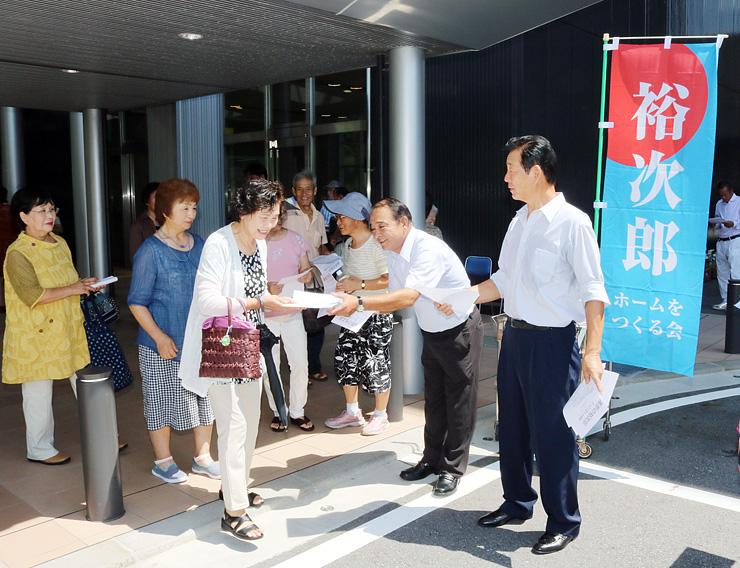 チラシを配布する上島代表(右)と池田委員長(右から2人目)