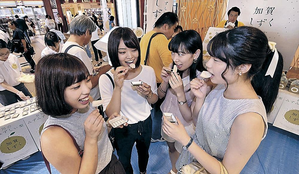 加賀しずくを試食する駅利用者=JR金沢駅