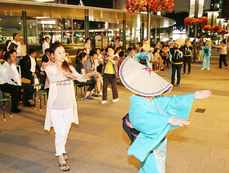 編みがさ姿の踊り手たちに見物客も加わった輪踊り=JR富山駅南口駅前広場