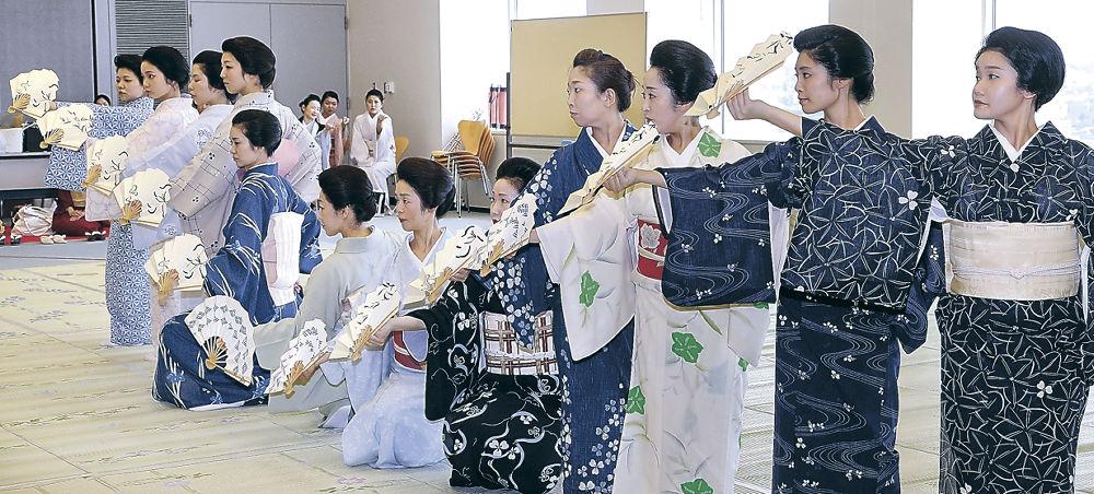 扇を連ねて逆さ富士を描く芸妓=北國新聞20階ホール