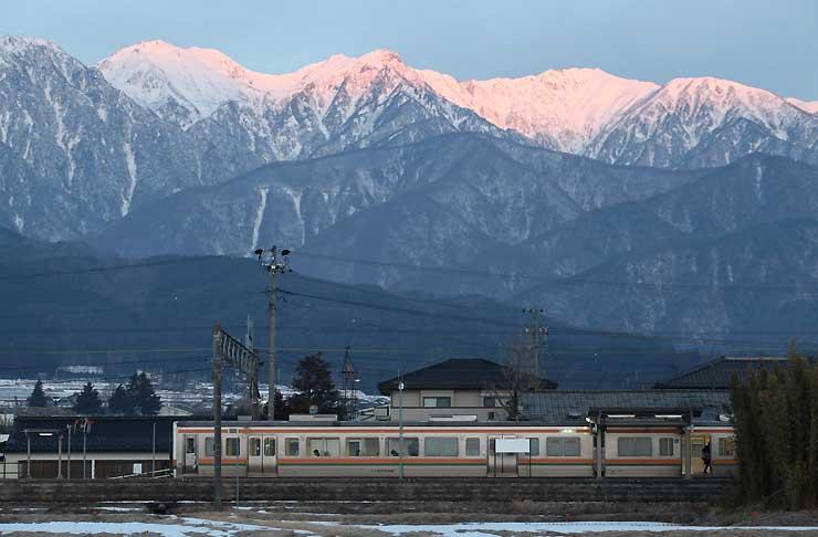 写真集に掲載した作品の一つ。飯島町の七久保駅で、朝日に赤く染まった中央アルプスを背景に停車する飯田線の列車