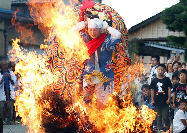 燃え盛る炎の中を駆け抜ける百足獅子=二口熊野社(写真部部長デスク・垣地信治)