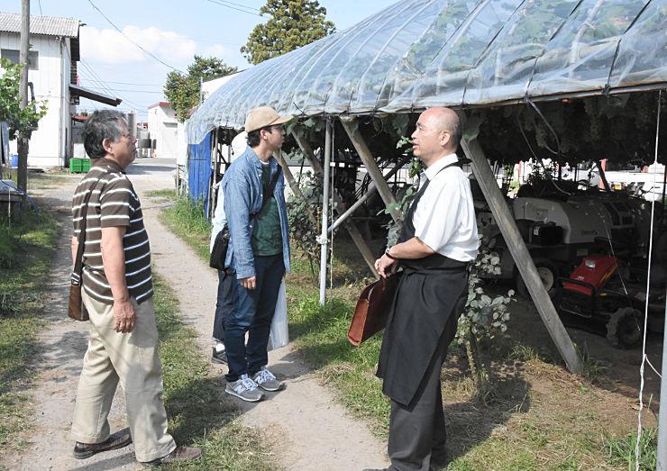 ガイド役の市職員(右)から農場を案内される参加者