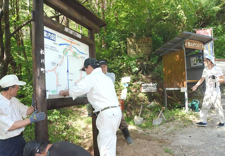 鳩打峠の登山口で看板を付け替える有志ら