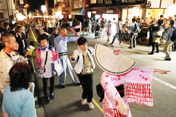 踊り手と一緒に「大輪踊り」を楽しむ観光客ら=富山市八尾町上新町