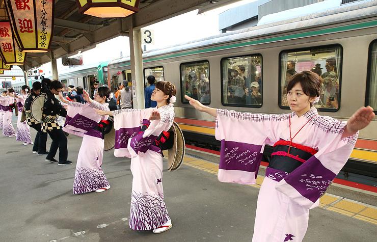 始発列車の乗客に見送りおわらを披露する踊り手=JR越中八尾駅