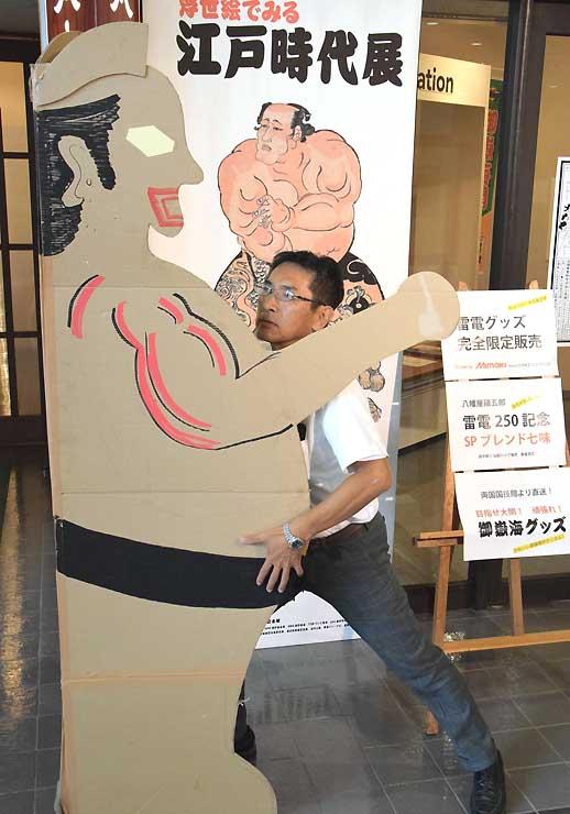 巨大紙人形の試作品と組み合う学芸員の佐藤さん