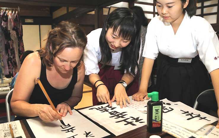 高校生(右2人)の手ほどきで書道に挑戦する外国人観光客。当て字で名前を書いた