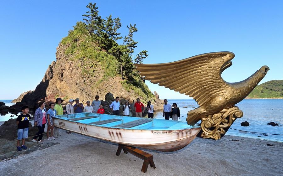 入り江に置かれた「船首方位と航路」に見入る来場者=珠洲市折戸町の木ノ浦海岸