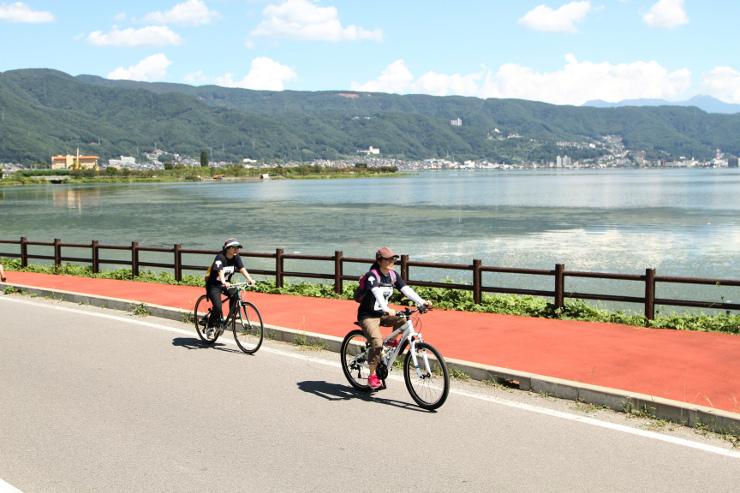 諏訪湖畔を自転車で快走するジャズマニアの参加者=岡谷市
