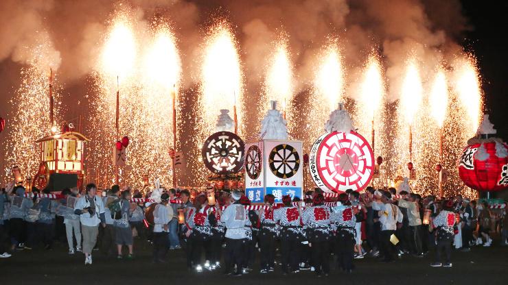 火の粉を降らす「連合大三国」の前でみこしを担ぐ人たち=9日午後9時22分、飯田市今宮町