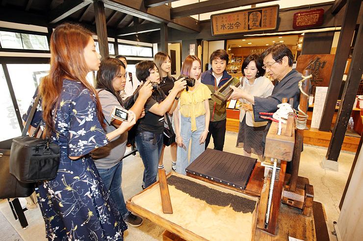 かつて使われていた道具で丸薬を作る作業を見学する東南アジアのブロガーたち=池田屋安兵衛商店