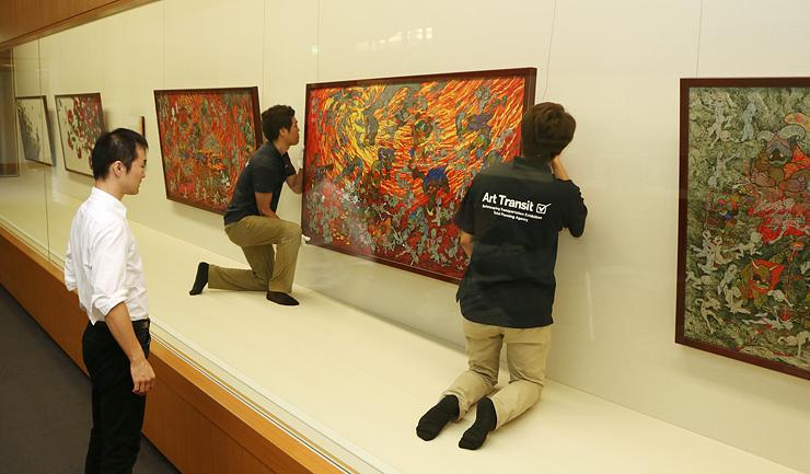 「地獄心音図」を壁に取り付ける展示スタッフ=県水墨美術館