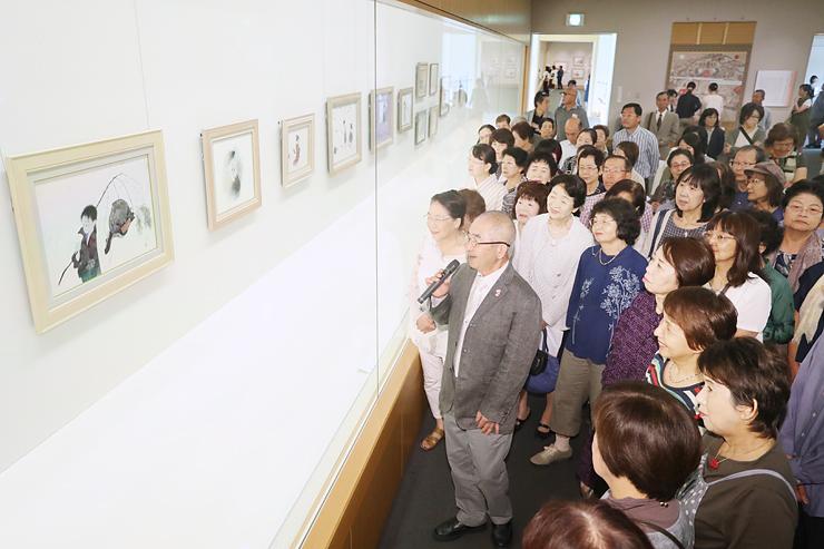 大勢の来場者に囲まれ、作品を解説する中島さん(中央)=県水墨美術館