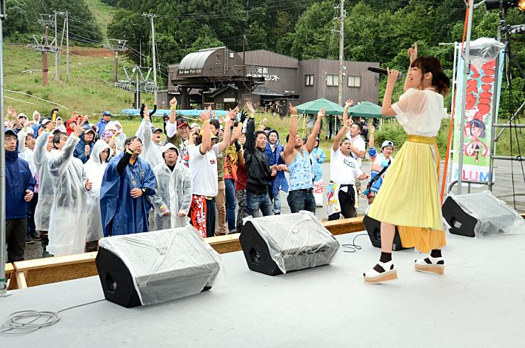 女性歌手(右)と一緒にアニメソングで盛り上がる観客たち