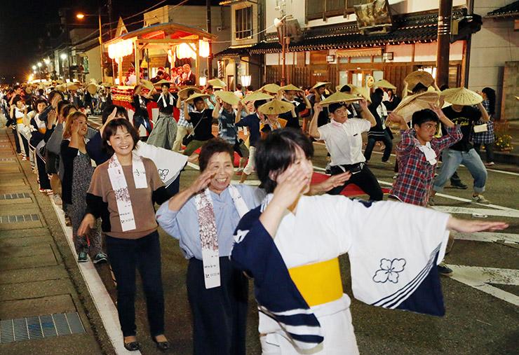 記念手拭いを首に掛け、観客と地元の踊り手が心行くまで楽しんだ総踊り=南砺市城端