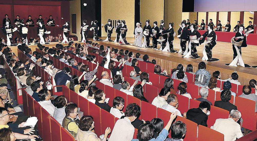 芸妓衆がまく手ぬぐいに手を伸ばす観客=金沢市の石川県立音楽堂邦楽ホール