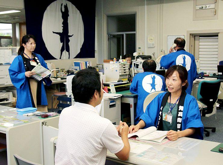 新調された角兵衛獅子の法被を着て業務に当たる月潟出張所の職員=新潟市南区