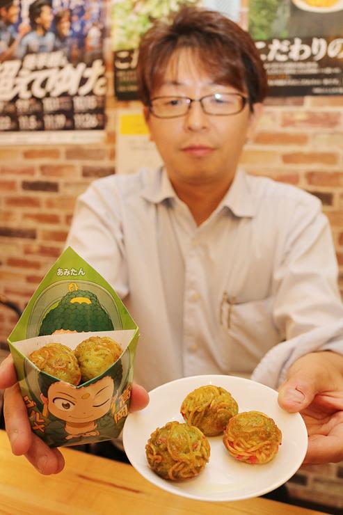 食べ歩きできるラーメンをコンセプトに開発した新商品。左のキャラクターをデザインした袋に入れて販売する