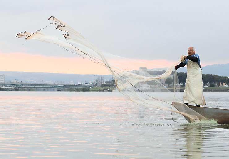 朝焼けに染まる諏訪湖で、ワカサギを狙って投網を放つ漁師