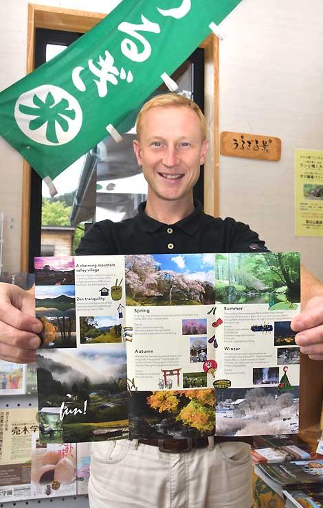 英語版の観光パンフレットを手にするニーザーさん。「村の良いところをたくさん紹介したい」と意気込む