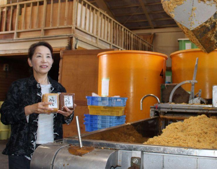 柳醸造で仕込まれたみそと同社の柳和子社長=26日、長岡市吉崎の同社