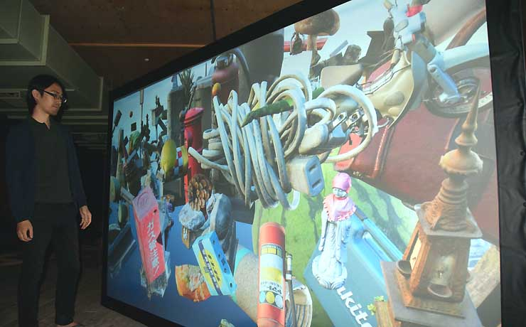 スクリーンに近づくとセンサーが反応し、投影した映像が拡大される作品。消火器やバイク、スイカなど身の回りにある物を撮影して立体化した