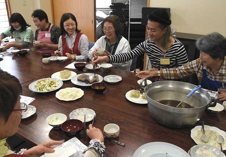 一緒に作った郷土料理を味わう滞在交流プログラムの参加者と住民