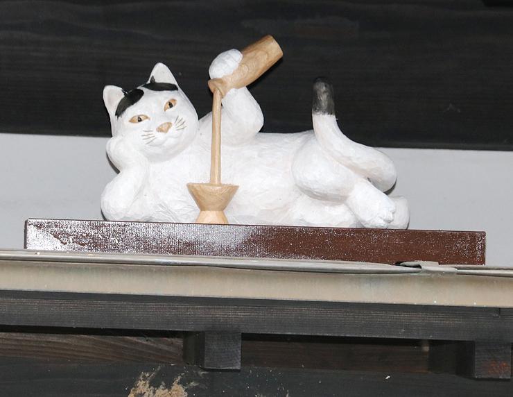 杯に酒を注ぐユニークな姿が目を引く木彫ネコ