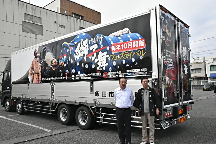 迫力ある屋台獅子の写真をあしらった大型トラックと、ラッピングを企画した冨内社長(左)