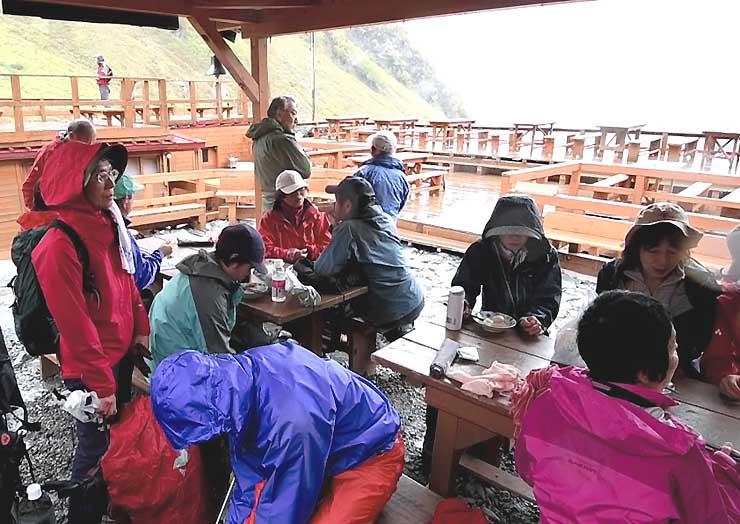 降り出した雨を避けて、涸沢ヒュッテの軒先で休む登山客