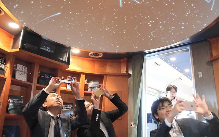 会員大会の合間に、ハイレールの車内にあるギャラリー兼プラネタリウムを写真に収める佐久青年会議所メンバー