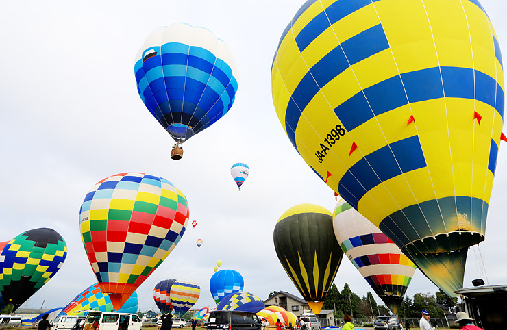 次々と空に浮かび上がるカラフルな熱気球=砺波市中村